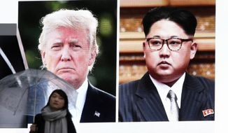 A woman walks by a huge screen showing U.S. President Donald Trump, left, and North Korea's leader Kim Jong Un, in Tokyo, Friday, March 9, 2018. After months of trading insults and threats of nuclear annihilation,  Trump agreed to meet with Kim by the end of May to negotiate an end to Pyongyang's nuclear weapons program, South Korean and U.S. officials said Thursday. No sitting American president has ever met with a North Korea leader. (AP Photo/Koji Sasahara)