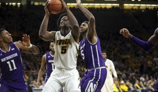 Iowa's Tyler Cook fights his way to the basket against Northwestern players in an NCAA college basketball game in Iowa City, Iowa, Sunday, Feb. 25, 2018. Iowa won, 77-70. (James Capen/Iowa City Press-Citizen via AP)