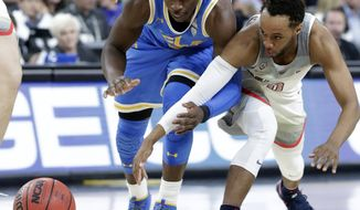 UCLA's Aaron Holiday, left, and Arizona's Parker Jackson-Cartwright reach for a loose ball during the first half of an NCAA college basketball game in the semifinals of the Pac-12 men's tournament Friday, March 9, 2018, in Las Vegas. (AP Photo/Isaac Brekken)
