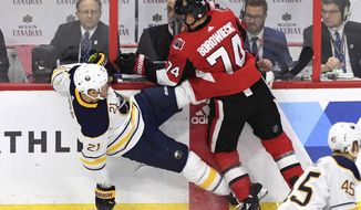 Ottawa Senators' Mark Borowiecki (74) checks Buffalo Sabres' Kyle Okposo (21) along the boards during first period NHL hockey action in Ottawa, Thursday, March 8, 2018. (Justin Tang/The Canadian Press via AP)