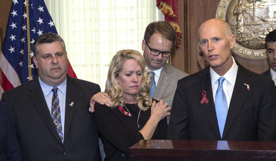 From left, Tony Montalto and wife Jennifer, parents of victim Gina Montalto, 14, and Ryan Petty who's daughter 14-year-old Alaina Petty who were both killed during the Marjory Stonemason Douglas High School shooting, comfort each other as they stand next to Florida Governor Rick Scott before he signs the Marjory Stoneman Douglas Public Safety Act in the Governor's office at the Florida Capital in Tallahassee, Fla., Thursday March 9, 2018. (AP Photo/Mark Wallheiser)