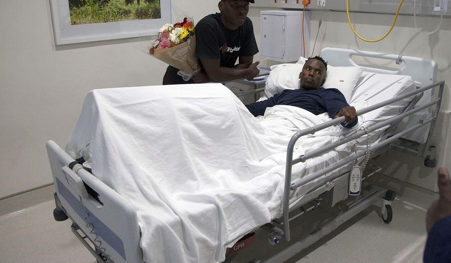 South African triathlete Mhlengi Gwala recovers from surgery in his hospital bed in Durban, South Africa, Friday, March 9, 2018. Gwala, who suffered severe injuries when attackers cut his legs with a saw, says he will focus on recovery so he can run and cycle again. (AP Photo/Khaya Ngwenya)