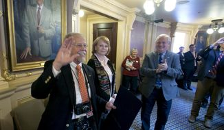 Richmond Times Dispatch Senior Photographer, Bob Brown, left, along with his wife, Evelyn, second from left, waves to legislators as he is honored on the floor of the House during the House session at the Capitol in Richmond, Va., Friday, March 9, 2018. Brown has covered the Virginia General Assembly since the 1970's. (AP Photo/Steve Helber)