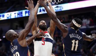 Washington Wizards forward Markieff Morris (5) goes to the basket between New Orleans Pelicans center Emeka Okafor (50) and guard Jrue Holiday (11) in the first half of an NBA basketball game in New Orleans, Friday, March 9, 2018. (AP Photo/Gerald Herbert)