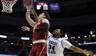 Saint Joseph's forward Pierfrancesco Oliva (24) is fouled by Rhode Island forward Andre Berry (34) during the second half of an NCAA college basketball game in the semifinals of the Atlantic 10 Conference tournament, Saturday, March 10, 2018, in Washington. Rhode Island won 90-87. (AP Photo/Alex Brandon)