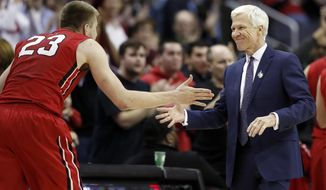 Davidson head coach Bob McKillop, right, greets forward Peyton Aldridge (23) as he leaves the game late in the second half of an NCAA college basketball game against St. Bonaventure at the Atlantic 10 Conference tournament, Saturday, March 10, 2018, in Washington. Davidson won 82-70. (AP Photo/Alex Brandon)