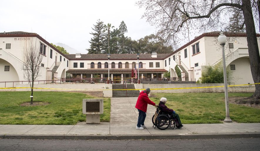 A man pushes a woman in a wheelchair past the Veterans Home of California, the morning after a hostage situation in Yountville, Calif., on Saturday, March 10, 2018.  A daylong siege at The Pathway Home ended Friday evening with the discovery of four bodies, including the gunman, identified as Albert Wong, a former Army rifleman who served a year in Afghanistan in 2011-2012. (AP Photo/Josh Edelson)