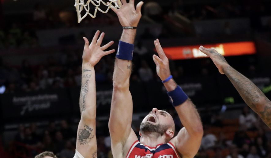 Washington Wizards' Marcin Gortat (13) is fouled by Miami Heat's Tyler Johnson (8) during the first half of an NBA basketball game, Saturday, March 10, 2018, in Miami. (AP Photo/Lynne Sladky)