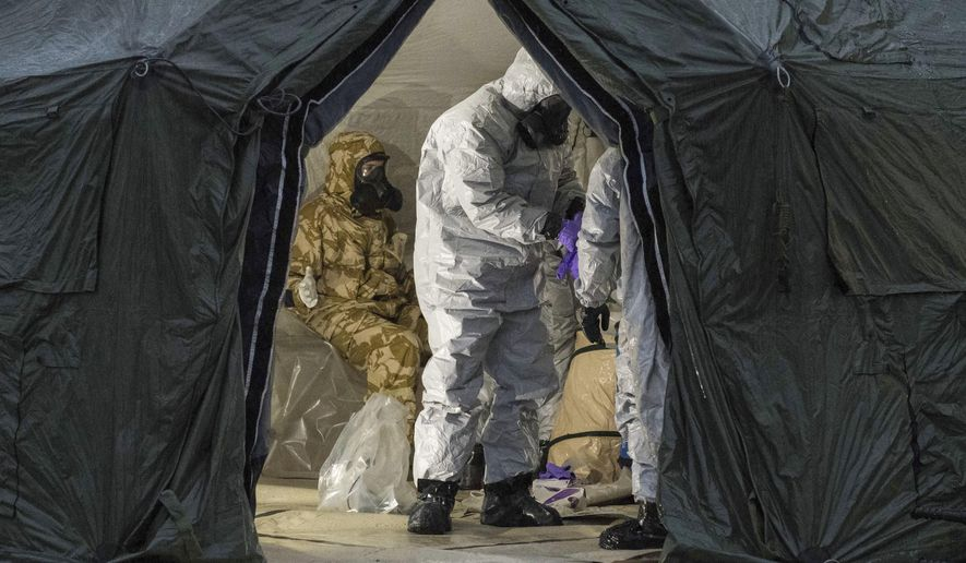 """Troops in protective gear as they work to remove a contaminated police car from the Accident and Emergency entrance at the District Hospital in Salisbury, England. Counter-terrorism police asked for military assistance to remove vehicles and objects from the scene in the city, much of which has been cordoned off over contamination fears of the nerve agent poisoning of former spy Sergei Skripal and his daughter. """"The United States shares the United Kingdom's assessment that Russia is responsible,"""" said White House press secretary Sarah Huckabee Sanders. (Pete Brown/MoD via AP)"""