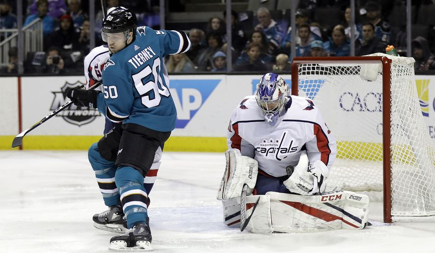 Washington Capitals goaltender Philipp Grubauer, right, stops a shot behind San Jose Sharks' Chris Tierney (50) during the first period of an NHL hockey game Saturday, March 10, 2018, in San Jose, Calif. (AP Photo/Marcio Jose Sanchez)