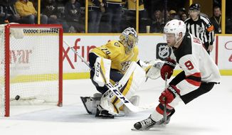 New Jersey Devils left wing Taylor Hall (9) scores a goal against Nashville Predators goalie Juuse Saros (74), of Finland, during a shootout at an NHL hockey game Saturday, March 10, 2018, in Nashville, Tenn. (AP Photo/Mark Humphrey)