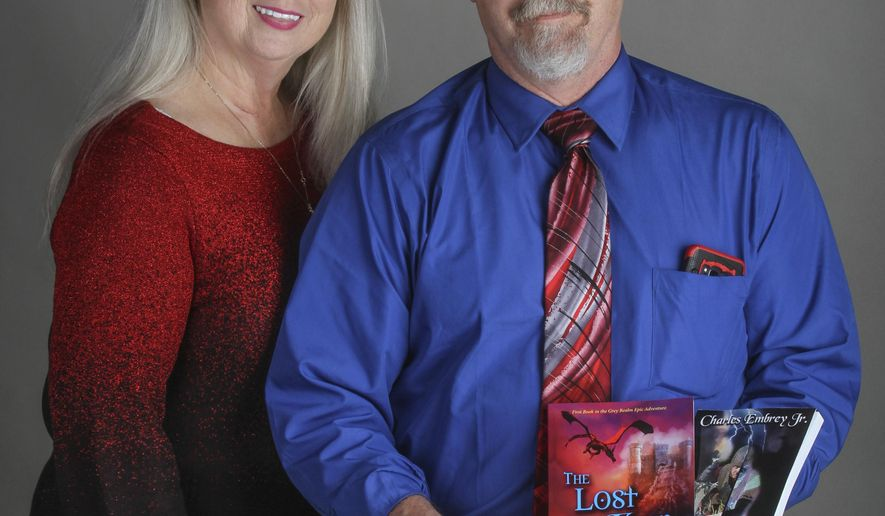 """In this Feb. 14, 2018 photo, Charles Embrey Jr., and his wife Barbara pose with his books, """"The Lost Keep"""" and """"Beyond the Black River Styx,"""" in Elizabethtown, Ky. Embrey Jr. exists in parallel universes. In one, he's married to Barbara Embrey, works as a pathologist assistant in Elizabethtown and is a grandpa to six. His other universe has dragons, female elf rangers, warrior princesses and Clovis, a protagonist who was chosen at 7 years old by the goddess Athena to be a holy warrior. (Greg Eans/The Messenger-Inquirer via AP)"""