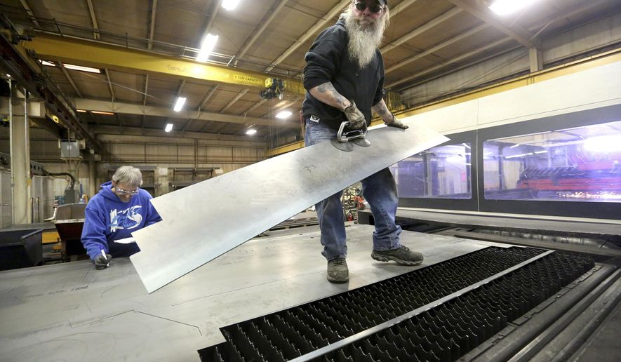 In this Feb. 23, 2018, photo, Robert Toms, left, and Rick Ross separate parts off the laser line at Henderson Products in Manchester, Iowa. Henderson Products specializes in making items for snow and ice removal, ranging from plows and ice scrapers to salt and sand spreaders. (Jessica Reilly/Telegraph Herald via AP)