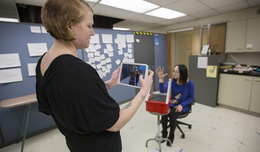 In a Tuesday, Feb. 27, 2018 photo, apparel studies senior Emily Seifert circles around Apparel studies PhD candidate Nokyeon Kim to complete a 3D scan of her hand at McNeal Hall. The scanner, which runs off an iPad, makes a virtual 3D model of the subject to help create ideal uniforms for occupations like firefighting.  (Ellen Schmidt/The Minnesota Daily via AP)