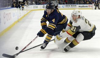 Buffalo Sabres defenseman Josh Gorges (4) is defended by Vegas Golden Knights center Cody Eakin (21) during the second period of an NHL hockey game, Saturday, March 10, 2018 in Buffalo, N.Y. (AP Photo/Adrian Kraus)