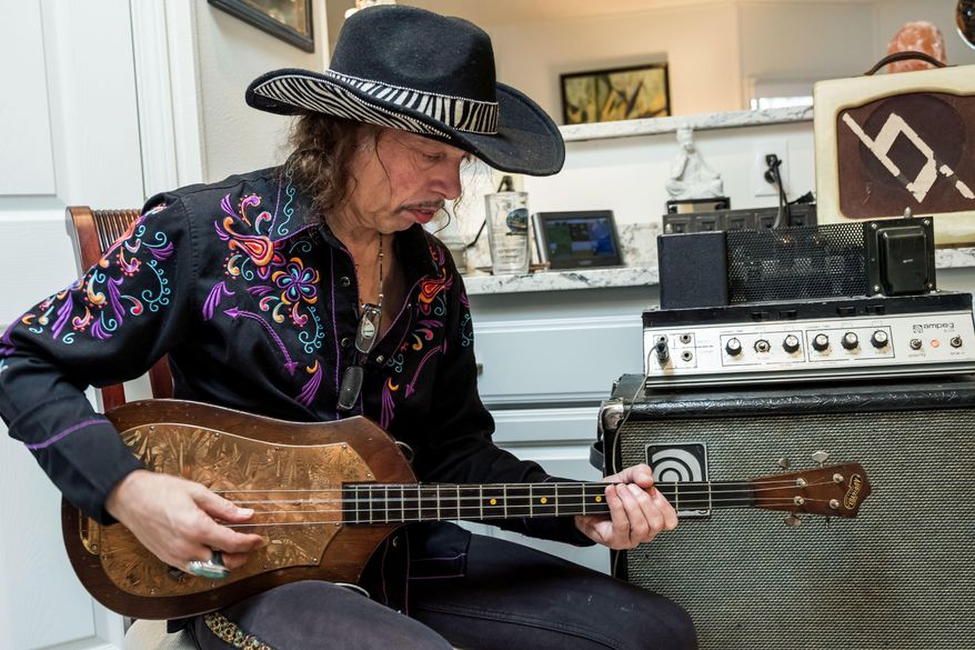 In this February 2018 photo, Randy Hansen plays an Audiovox Model 736 electric bass guitar made by Seattle builder Paul Tutmarc in the mid-1930s,  in the Seattle kitchen of Bev and Dale McKnight, who bought the guitar from Tutmarc decades ago and are selling it on eBay. (Dean Rutz /The Seattle Times via AP)