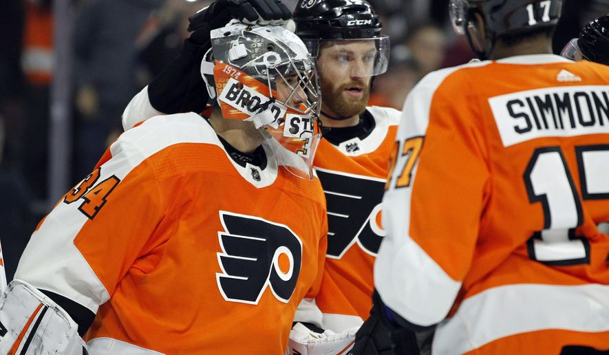 Philadelphia Flyers goalie Petr Mrazek, left, and Sean Couturier, center, celebrate the 2-1 win over the Winnipeg Jets at the end of an NHL hockey game Saturday, March 10, 2018, in Philadelphia. (AP Photo/Tom Mihalek)