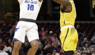 Buffalo's Wes Clark (10) shoots against Toledo's Marreon Jackson (3) during the first half of an NCAA college basketball championship game of the Mid-American Conference tournament, Saturday, March 10, 2018, in Cleveland. (AP Photo/Tony Dejak)