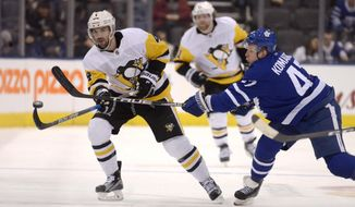 Pittsburgh Penguins defenseman Justin Schultz (4) chips the puck past Toronto Maple Leafs center Leo Komarov (47) during the third period of an NHL hockey game Saturday, March 10, 2018, in Toronto. (Jon Blacker/The Canadian Press via AP)