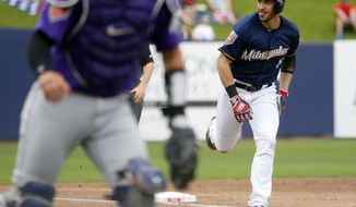 Milwaukee Brewers' Ryan Braun scores on a throwing error during the first inning of a spring training baseball game against the Colorado Rockies, Saturday, March 10, 2018, in Phoenix. (AP Photo/Matt York)