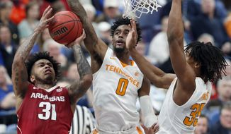 Arkansas' Anton Beard (31) shoots as Tennessee's Jordan Bone (0) and Yves Pons, right, defend during the first half of an NCAA college basketball semifinal game at the Southeastern Conference tournament Saturday, March 10, 2018, in St. Louis. (AP Photo/Jeff Roberson)