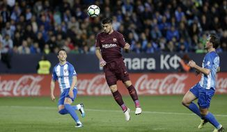 Barcelona's Luis Suarez, jumps for the ball next to Malaga's Ricca, left, and Miquel, right, during a Spanish La Liga soccer match between Malaga and Barcelona in Malaga, Spain, Saturday, March 10, 2018. (AP Photo/M.Pozo)