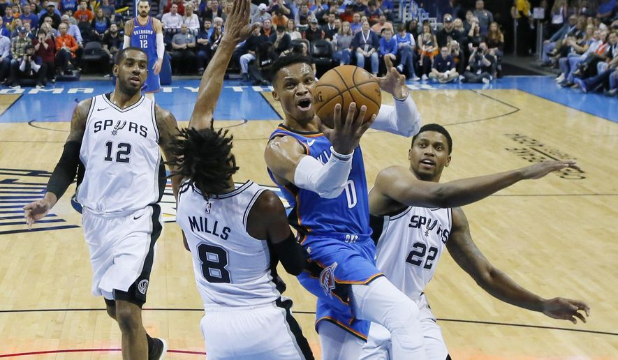 Oklahoma City Thunder guard Russell Westbrook (0) goes to the basket between San Antonio Spurs guard Patty Mills (8) and forward Rudy Gay (22) in the first half of an NBA basketball game in Oklahoma City, Saturday, March 10, 2018. (AP Photo/Sue Ogrocki)