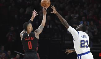 Portland Trail Blazers guard Damian Lillard hits a 3-point shot over Golden State Warriors forward Draymond Green during the first half of an NBA basketball game in Portland, Ore., Friday, March 9, 2018. (AP Photo/Steve Dykes)