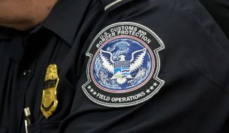 A customs agent wears a patch for the U.S. Customs and Border Protection agency, which is a part of the Department of Homeland Security, Friday, Oct. 27, 2017, at John F. Kennedy International Airport in New York. (AP Photo/Mark Lennihan)