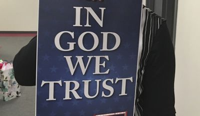 """Wyoming state Rep. Cheri Steinmetz, R-Lingle, on Tuesday, March 6, 2018, shows an example of an """"In God We Trust"""" placard in Cheyenne, Wyo. Steinmetz is sponsoring a bill that would allow people to donate such placards for display in prominent places in state buildings and schools. Her bill has been approved by the state House and is now being considered in the state Senate, winning the endorsement of a Senate committee on Tuesday. (AP Photo by Bob Moen)"""