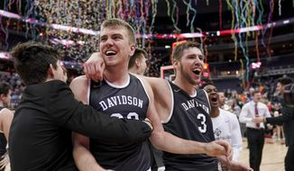 Davidson forward Peyton Aldridge (23), second from left, guard Jon Axel Gudmundsson (3), right, and others celebrate after an NCAA college basketball championship game against Rhode Island in the Atlantic 10 Conference tournament, Sunday, March 11, 2018, in Washington. (AP Photo/Andrew Harnik)