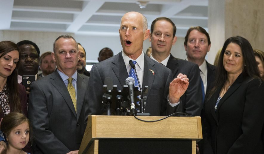 Florida Gov. Rick Scott speaks after the end of the legislative session at the Florida State Capitol in Tallahassee, Fla., Sunday, March 11, 2018. Flanking Scott is Speaker of the House Richard Corcoran, left, and Senate President Joe Negron. (AP Photo/Mark Wallheiser)