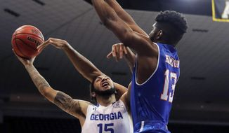 Georgia State guard D'Marcus Simonds (15) goes to the basket against Texas-Arlington center Johnny Hamilton (13) in the first half of the the Sun Belt Conference NCAA college basketball championship game in New Orleans, Sunday, March 11, 2018. (AP Photo/Gerald Herbert)