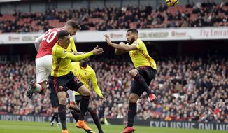 Arsenal's Shkodran Mustafi, left, heads the ball to score his side's opening goal during the English Premier League soccer match between Arsenal and Watford at the Emirates stadium in London, Sunday, March 11, 2018. (AP Photo/Matt Dunham)