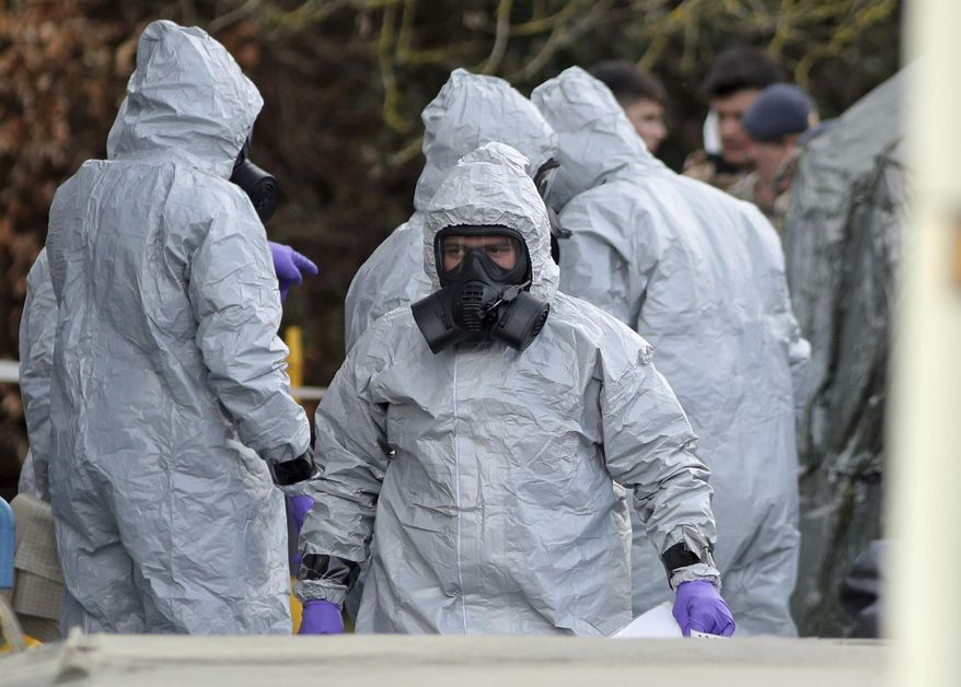 Investigators in protective clothing prepare to move an ambulance at the South Western Ambulance Service station in Harnham, near Salisbury, England, as police and members of the armed forces probe the suspected nerve agent attack on Russian spy double agent Sergei Skripal, Saturday March 10, 2018. Counter-terrorism police asked for military assistance to remove vehicles and objects from the scene in the city, much of which has been cordoned off over contamination fears of the nerve agent poisoning of former spy Sergei Skripal and his daughter. (Andrew Matthews/PA via AP)