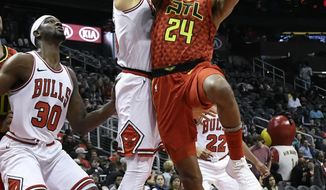 Atlanta Hawks guard Kent Bazemore (24) shoots as Chicago Bulls forward Denzel Valentine and Chicago Bulls forward Noah Vonleh (30) defend during the first half of an NBA basketball game Sunday, March 11, 2018, in Atlanta. (AP Photo/John Amis)