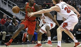 Atlanta Hawks forward Taurean Prince, left, drives as Chicago Bulls forward Lauri Markkanen, of Finland, right, defends during the first half of an NBA basketball game Sunday, March 11, 2018, in Atlanta. (AP Photo/John Amis)