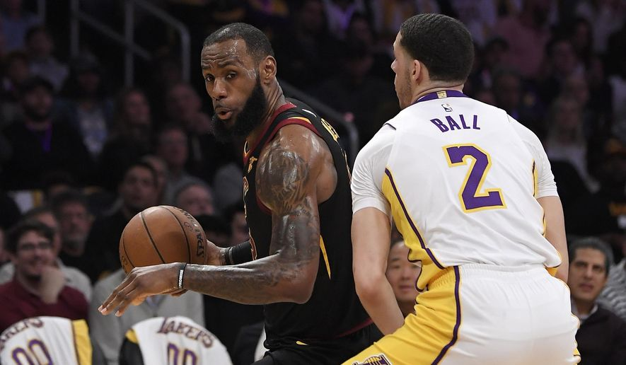 Cleveland Cavaliers forward LeBron James, left, tries to get past Los Angeles Lakers guard Lonzo Ball during the first half of an NBA basketball game, Sunday, March 11, 2018, in Los Angeles. (AP Photo/Mark J. Terrill)