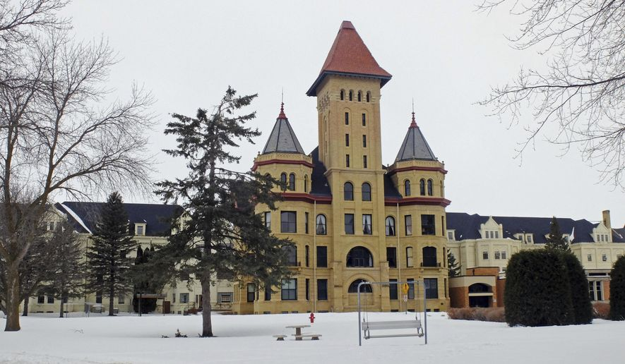 This March 2, 2018 photo shows the Fergus Falls State Hospital main administration building in Fergus Falls, Minn.   Constructed in the late 1800s, city leaders have wrestled for more than decade with what to do with the iconic structure that once housed as many as 2,000 patients treated for a variety of mental illnesses.  (Dan Gunderson/Minnesota Public Radio via AP)
