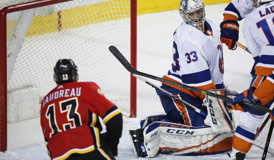 New York Islanders goalie Christopher Gibson, right, of Finland, looks back as the Calgary Flames score during third period NHL hockey action in Calgary, Alberta, Sunday, March 11, 2018. (Jeff McIntosh/The Canadian Press via AP)