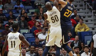 Utah Jazz center Rudy Gobert (27) shoots as New Orleans Pelicans center Emeka Okafor (50) defends the play in the first half of an NBA basketball game in New Orleans, Sunday, March 11, 2018. (AP Photo/Scott Threlkeld)