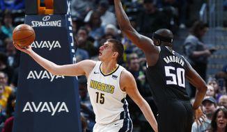 Denver Nuggets center Nikola Jokic, left, drives past Sacramento Kings forward Zach Randolph for a basket in the first half of an NBA basketball game Sunday, March 11, 2018, in Denver. (AP Photo/David Zalubowski)