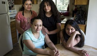 In this March 3, 2018 photo, Bernarda Pineda, of Marysville, Wash., was notified on Feb. 20 that she was being deported to Honduras, the country she fled from 12 years ago in an attempt to escape from political instability, impoverished and dangerous conditions, particularly for women. Her daughters, Sherly, left, 14, Stacey, 9, and Sheyla, 11, face an uncertain future without their mother, who is set to depart the U.S. on March 19, and will need to relocate to Chicago to live with their father.  (Ian Terry/The Herald via AP)