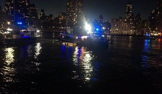 """This image made from video provided by the New York City Police Department shows the scene of a helicopter crash in the East River in New York on Sunday, March 11, 2018. A Federal Aviation Administration spokeswoman said Sunday the Eurocopter AS350 went down just after 7 p.m. Sunday in the waterway just north of Roosevelt Island and is """"reportedly inverted in the water."""" (New York City Police Department via AP)"""