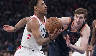 Toronto Raptors guard DeMar DeRozan, left,  drives to the basket past New York Knicks forward Luke Kornet, right, during the first half of an NBA basketball game, Sunday, March 11, 2018, at Madison Square Garden in New York. (AP Photo/Mary Altaffer)