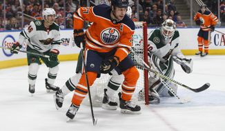 Minnesota Wild goaltender Devan Dubnyk (40) looks for the puck as Edmonton Oilers left wing Milan Lucic (27) comes around the net during the second period of an NHL hockey game Saturday, March 10, 2018, in Edmonton, Alberta. (Jason Franson/The Canadian Press via AP)