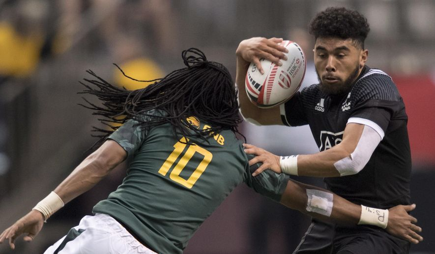 Ngarohi McGrarvey Black, of New Zealand, tries to keep the ball from Cecil Afrika, of South Africa, at the World Rugby Seven Series in Vancouver, British Columbia, Saturday, March, 10, 2018. (Jonathan Hayward/The Canadian Press via AP)