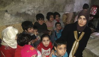 This Sunday, March 11, 2018, photo, provided by Deana Lynn, from Detroit, Michigan, shows her, with her kids and other Syrian children at a shelter where they hide from Russian and Syrian government forces airstrikes, in eastern Ghouta, a suburb of the Syrian capital Damascus. Lynn is calling on President Donald Trump to put more pressure on Russia to stop bombing us amid an air and ground assault by government forces that has killed more than 1,000 people over the past three weeks. Lynn and her family are among nearly 400,000 people who are trapped in eastern Ghouta. (Deana Lynn via AP)