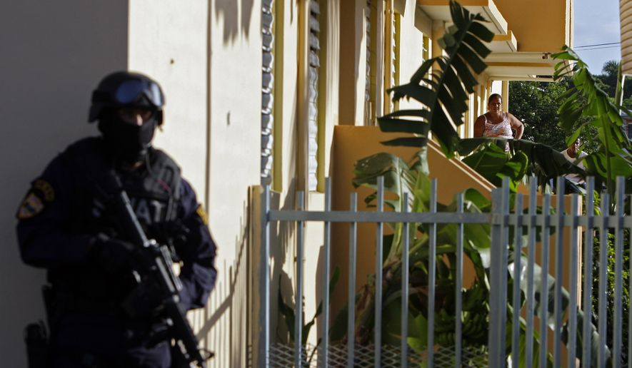 A resident of a public housing project (behind right) watches police conduct an anti-drug raid in Mayaguez, Puerto Rico, on July 9, 2010. (Associated Press) **FILE**