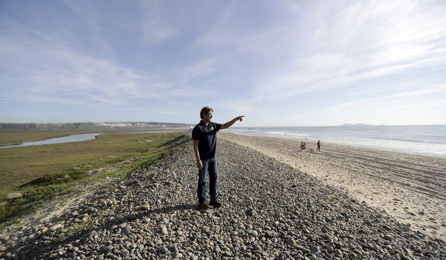 "Imperial Beach Mayor Serge Dedina points towards a beach that was closed due to sewage water contamination as it flowed from Tijuana, Mexico, behind, through the Tijuana River, left, and out to sea Friday, March 3, 2017, in Imperial Beach, Calif. Dedina has called it, ""the tsunami of sewage spills."" For more than two weeks last month, a stench of feces, ammonium and laundry detergent wafted through the air in Imperial Beach. Sewer repair work in Tijuana, caused an estimated 143 million gallons to spill into the United States and the Pacific Ocean for 18 days. A Mexican official challenged those findings on Friday after a week of public uproar. (AP Photo/Gregory Bull)"